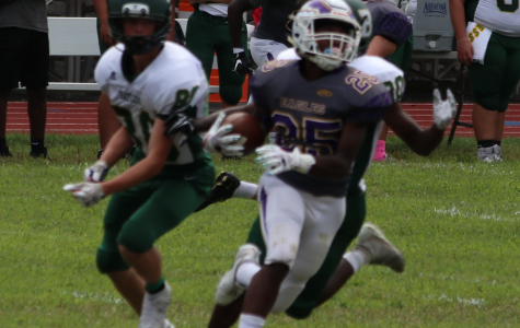 Xavier Lane (junior) rushes with the ball, fighting hard for the win