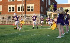 Senior Henry Ritter bursts through the cheerleaders banner as the game begins.
